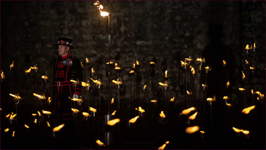 Lone Beefeater amongst a dea of flame in the Tower Moat