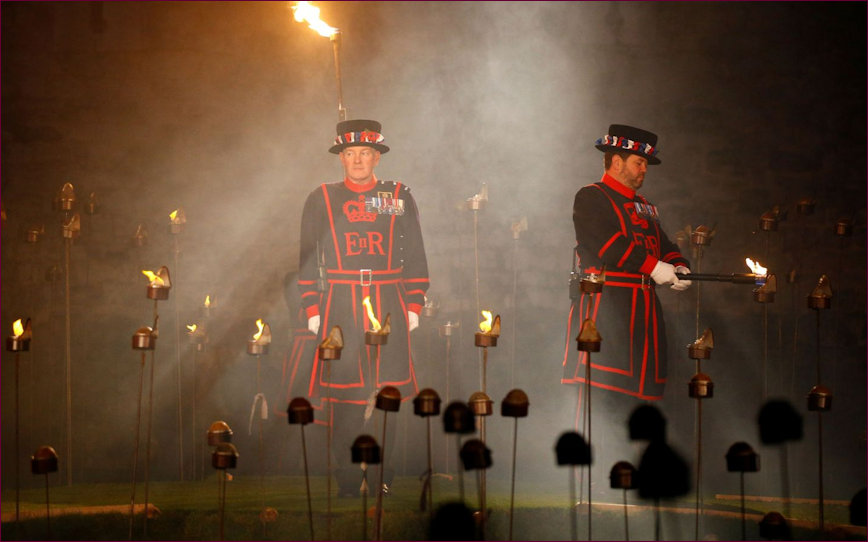 Two Beefeaters, one lighting the torches one keeping an eye on proceedings