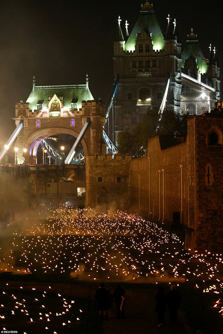 Tower Bridge mysteriously lit overlooking the moat filled with lit torches