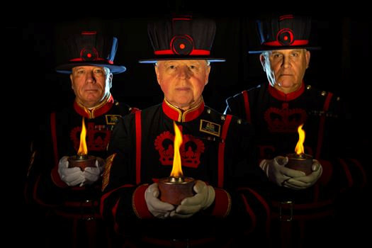 Three Beafeaters lighting torches and keeping vigil