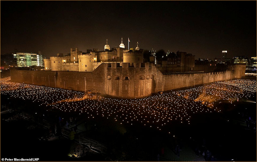 Panorama of illuminated Tower of London and moat filled with torches