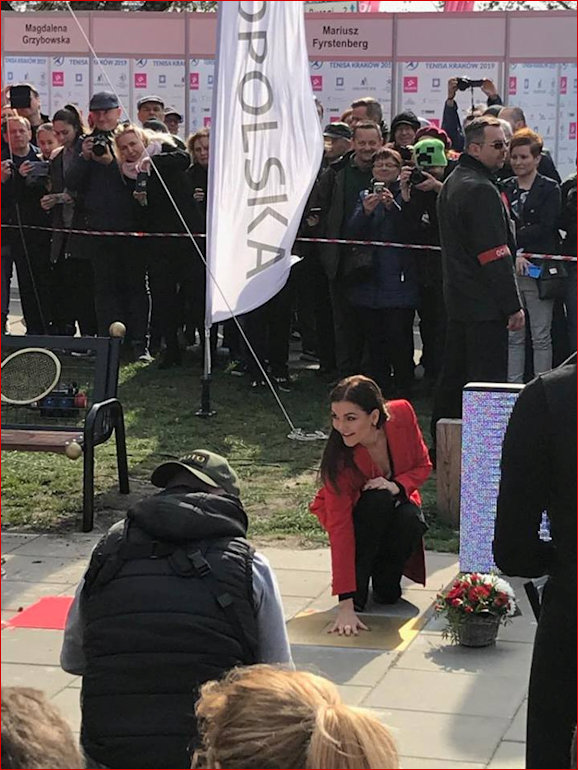Aga kneeling by her handprint plaque