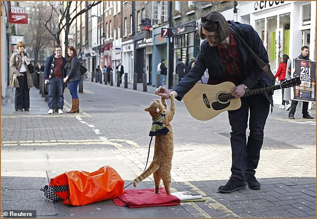 Streetwise Bob busking with his owner